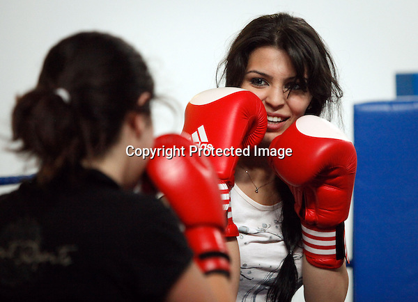 Haneen (L) and Raya (R), exchange punches as they train inside the training hall at al-Hussein sport city complex, in Amman, Jordan on June 06, 2010. (Salah Malkawi)