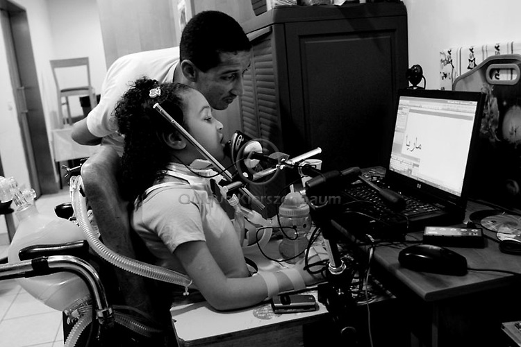 Mariya Amin works on a special computer helped by her father Hamdi in Alyn, a rehabilitation hospital in Jerusalem, October 12,2007..Photo by Quique Kierszenbaum...