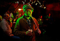 "Matthew Murray, from Co. Meath, waits to perform karaoke in a nightclubduring the annual ""Culchie Festival,"" in the town of Athboy. The festival embraces the stereotypes of the Ireland's rural farmers, and provides an excuse for participants to run amok drinking and carousing through mock contests, as well as nearby towns, farms, pubs, and even wedding parties. The derogatory term ""culchie,"" similar to ""redneck,"" is used by natives of urban areas, especially Dublin, to describe people from outside the city. The word is reported to stem from the phrase ""culturally retarded"" or from those that studied ""agriculture."".."