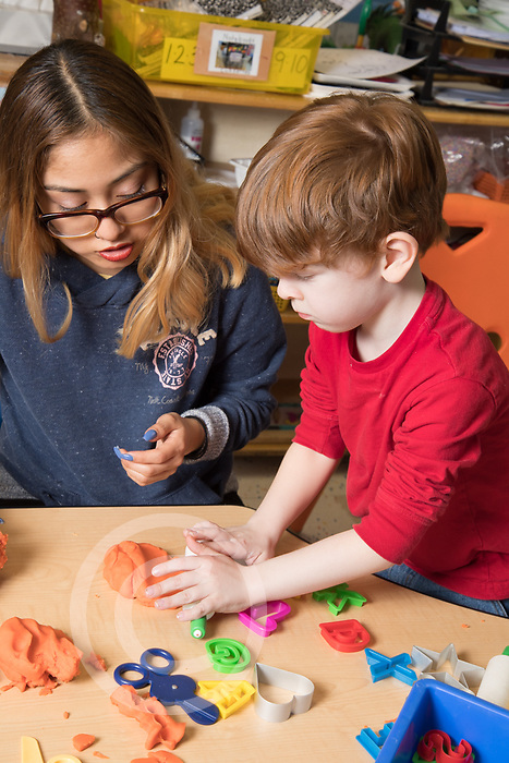 Education Preschool classroom scenes 3-4 year old student teacher working with boy in classroom, play dough activity