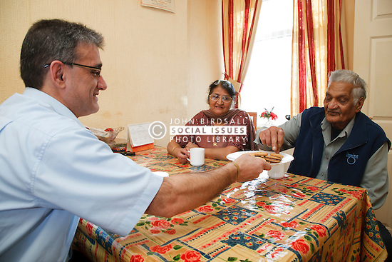 Elderly south Asian parents and son having tea and biscuits.