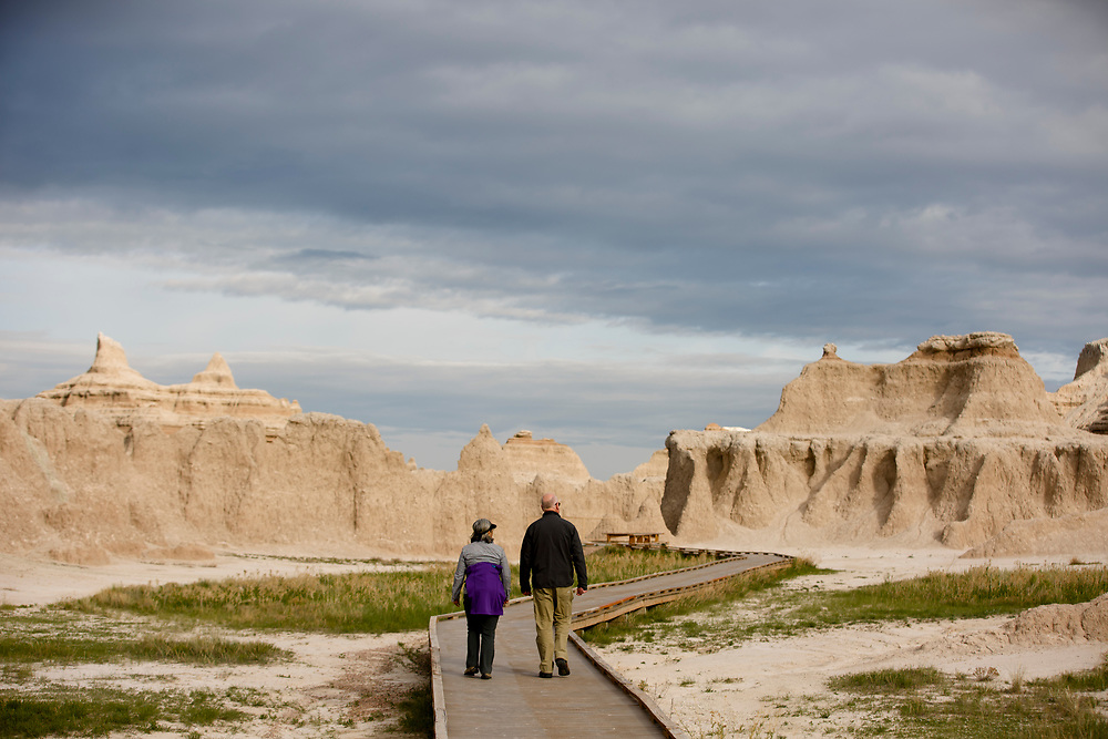 A couple walks a boardwalk in Badlands National Park, South Dakota on Saturday, May 20, 2017. (Photo by James Brosher)