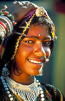 Smiling young woman wearing ornate, traditional jewelry and headdress. Caste mark. Face. Rajasthan India Asia.
