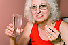 Woman taking medication with a glass of water,