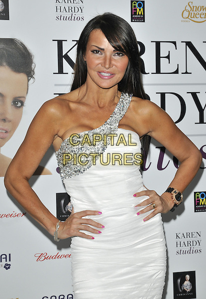 LIZZIE CUNDY .At the Chelsea Summer Gala, Wyndham Grand Hotel, Chelsea Harbour, London, England, 23rd July 2010..half length white one shoulder dress hands on hips silver beaded wrist watch black .CAP/CAN.©Can Nguyen/Capital Pictures.