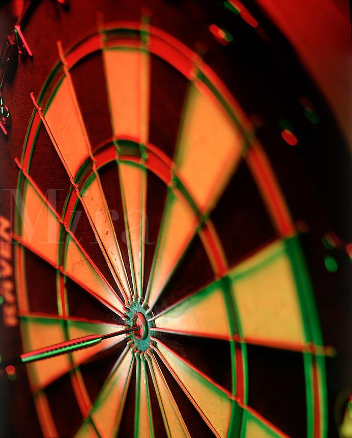 Dart board with dart hitting the bulls-eye.