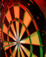 Dart board with dart hitting the bulls-eye.