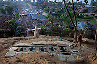 An elderly Rohingya Muslim man walks past open latrines at a camp for Rohingya people.