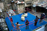 38 year old wrestler Carmen Rosa (fighting name), Polonia Ana Choque Silvestre (real name), centre (in yellow), fights with fellow wrestler 26 year old Yolanda La Amorosa (fighting name), Veraluz Cortez (real name) on a practice ring at the back of Polonia's house. Polonia and Veraluz are Cholitas, wrestlers of native Aymara descent. When Cholitas fight they wear traditional costume. Polonia and Veraluz fight with the lucha libre (free wrestling) group Los Diosas del Ring. ...