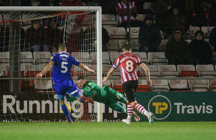 Lincoln City's Grant Smith saves at the feet of Morecambe's Steven Old<br /> <br /> Photographer Chris Vaughan/CameraSport<br /> <br /> The EFL Sky Bet League Two - Saturday 15th December 2018 - Lincoln City v Morecambe - Sincil Bank - Lincoln<br /> <br /> World Copyright © 2018 CameraSport. All rights reserved. 43 Linden Ave. Countesthorpe. Leicester. England. LE8 5PG - Tel: +44 (0) 116 277 4147 - admin@camerasport.com - www.camerasport.com