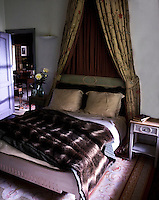 A canopied bed accessorised with a faux fur blanket and gold colour pillows creates an opulent bedroom