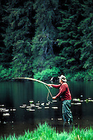 A fly fisherman casts his line on Hasselborg Lake, Admiralty Island, Alaska in the Tongass National Forest. (Southeast Alaska). Alaska, Admiralty Island, Hasselborg Lake, Tongass National Forest.