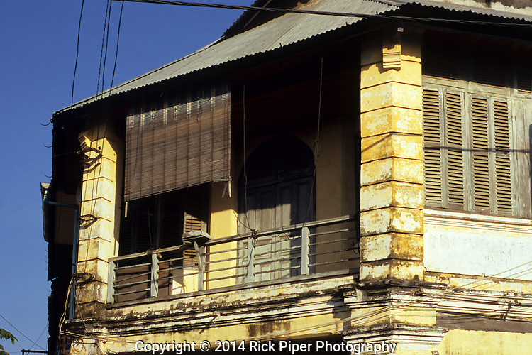 Weathered decaying wooden shuttered facade and balcony of old French colonial building in the centre of Kampot, Cambodia.