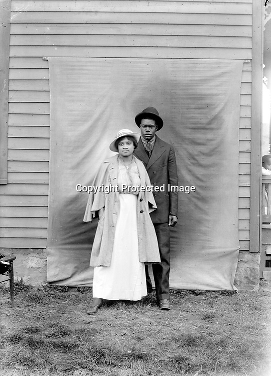 YOUNG COUPLE. The few surviving vintage prints from John Johnson photographs suggest that he might have intended to crop an image like this one, excluding all but the couple and a portion of his backdrop. But the full-frame negative brings the scene to life, showing his backdrop tacked against the side of a clapboard house, with an old chair to the left and a small child observing the activity from the right edge.<br /> <br /> Photographs taken on black and white glass negatives by African American photographer(s) John Johnson and Earl McWilliams from 1910 to 1925 in Lincoln, Nebraska. Douglas Keister has 280 5x7 glass negatives taken by these photographers. Larger scans available on request.