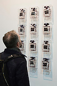27 February 2014, London, United Kingdom. Pictured: a man looks at a sculpture of what seems to be perfume bottles but they carry the names of places where protesters clashed with the state, such as Kiev. Unknown artist. The Art14 Art Fair at Olympia Grand Hall, London, opens its doors to the public from 28 February to 2 March 2014. Art14 London features 180 galleries from 40 countries with works from emerging talents to modern masters.