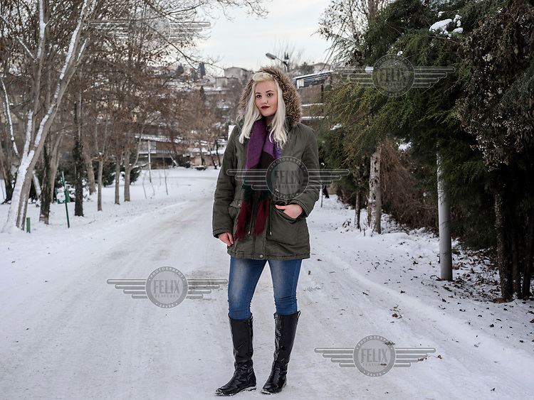 A young woman stands outside in the snow.