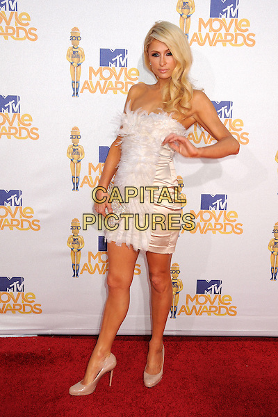 PARIS HILTON .MTV Movie Awards 2010 - Arrivals held at the Gibson Amphitheatre, Universal City, California, USA, 6th June 2010..full length white strapless cream feather feathers dress hand trim beige nude shoes clutch bag tanned patent silver sparkly .CAP/ADM/BP.©Byron Purvis/AdMedia/Capital Pictures.