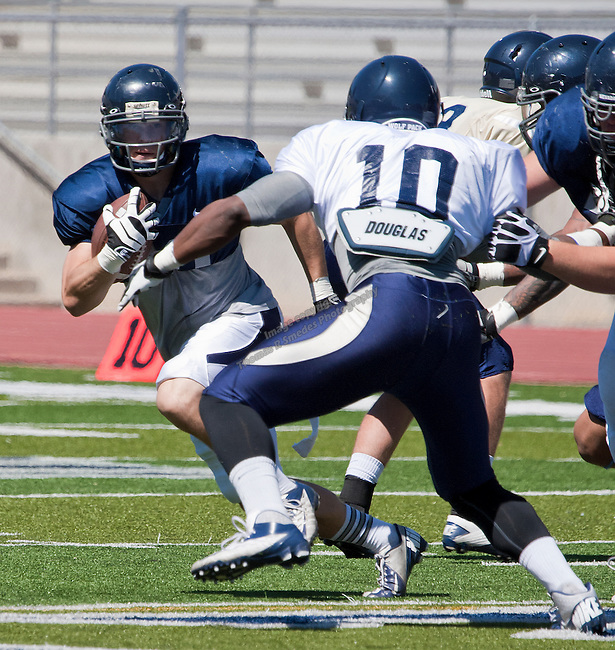 Blue team running back Kendall Brock runs around Silver team defender Reggie Coates during the Nevada football team's final scrimmage of spring, the Silver & Blue Game, held at Mackay Stadium on Saturday, April 20, 2013.
