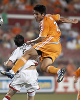 Houston Dynamo forward Brian Ching (25) takes to the air over New England Revolution defender Jay Heaps (6).  New England Revolution beat Houston Dynamo 1-0 at Robertson Stadium in Houston, TX on May 19, 2007.
