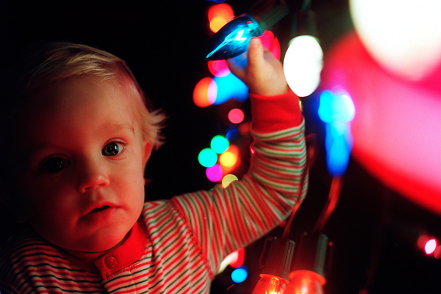 A young boy looks at Christmas lights.