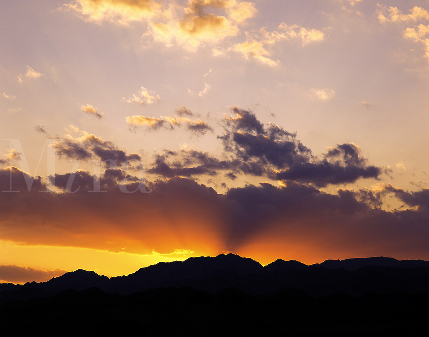 Sunset sky in the Negev desert north of Eilat, with the sun going down behind a range of silhouetted rocky hills; Israe