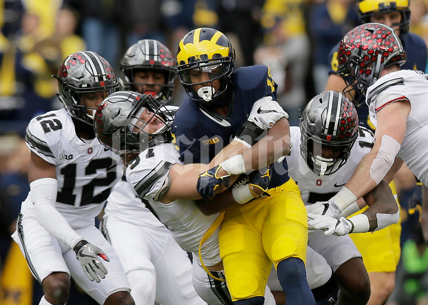 Ohio State Buckeyes defensive lineman Nick Bosa (97) tackles Michigan Wolverines running back Chris Evans (12) during the first quarter of the NCAA football game at Michigan Stadium in Ann Arbor on Nov. 25, 2017. [Adam Cairns/Dispatch]