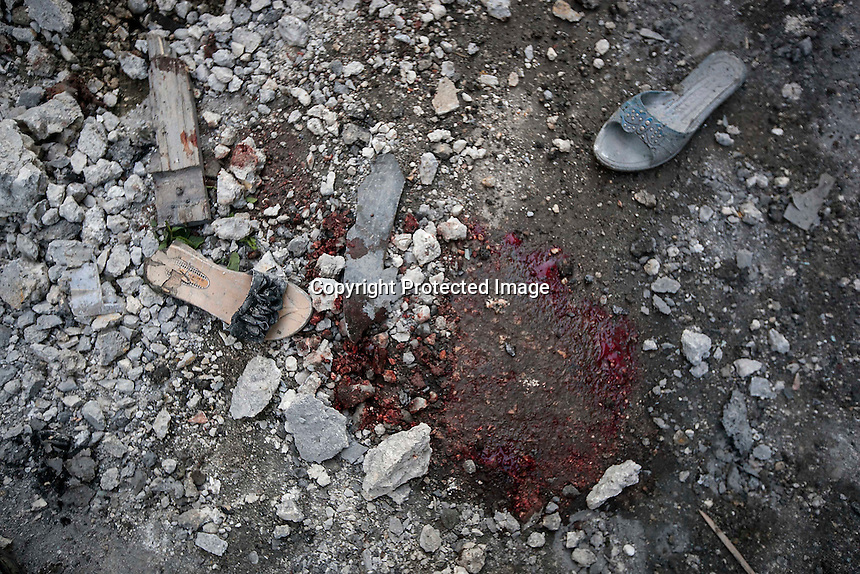 In this Sunday, Dec. 02, 2012 photo, a puddle of blood is seen beside shoes of Syrian residents st one street outside a bakery in Hullok district after a mortar shell hit the bakery killing four and injuring  another two in Hullok district during heavy shelling in Aleppo, the Syrian's largest city. (AP Photo/Narciso Contreras)