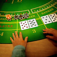 A dealer reveals his hand in a game of Baccarat, a popular casino game .