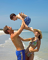 Caucasian father lifts son into the air while mom watches, all laughing , Ft. Desoto beach, St. Petersburg, Florida, USA.