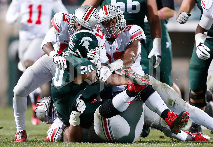 Ohio State Buckeyes cornerback Eli Apple (13), Ohio State Buckeyes linebacker Joshua Perry (37) and Ohio State Buckeyes defensive tackle Michael Bennett (63) come together to take down Michigan State Spartans running back Nick Hill (20) in the second quarter of the college football game between the Ohio State Buckeyes and the Michigan State Spartans at Spartan Stadium in East Lansing, Saturday night, November 8, 2014. As of half time the Ohio State Buckeyes led the Michigan State Spartans 28 - 21. (The Columbus Dispatch / Eamon Queeney)