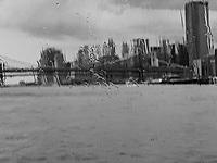 View through NYC ferry's window in rainstorm of Brooklyn Bridge and lower Manhattan skyline.