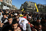 Mourners carry the body of Palestinian Hasan Nofal 17, who was died of his wounds which he sustained by Israeli forces during clashes in tents protest where Palestinians demand the right to return to their homeland at the Israel-Gaza border, during his funeral at al-Bureij in the central of Gaza Strip on February 13, 2019. Photo by Ashraf Amra