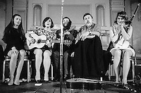 Ewan MacColl (second from left), singer, song writer, dramatist, playright, political activist (real name, Jimmie Miller) and Peggy Seeger (far right), song writer and performer (and member of the North American Seeger folk family) at a folk club in London around the late 1960s.  If you can identify the venue, please let me know.