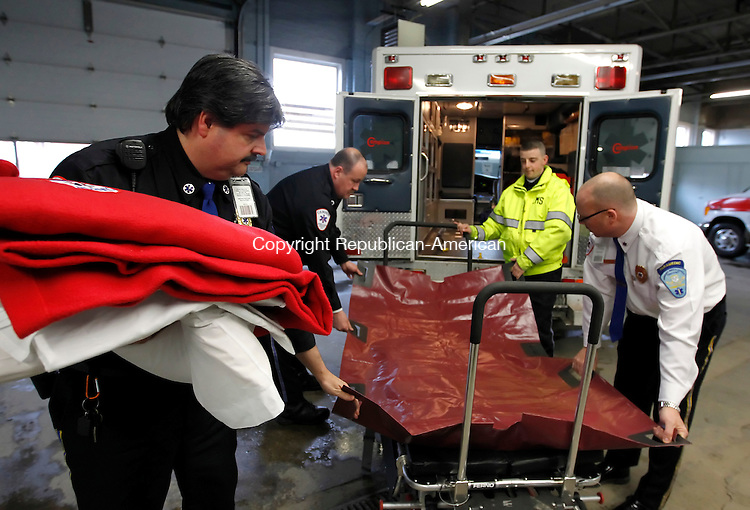 Waterbury, CT- 25, February 2011-022511CM08 (L-R) Paramedic Supervisor Robert Murray, Paramedic Jon St Louis, EMT Mark Pinto and Operations Director John Zarrella demonstrate a Stryker Ambulance Stretcher Friday afternoon at the Campion headquarters in Waterbury.  The stretcher, which is approximately 10 inches wider then     regular stretchers, can carry 700 lbs and is used for obese patients. Christopher Massa Republican-American