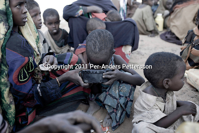 DADAAB, KENYA - JULY 31: A child drinks water as Somali refugees arrive early in the morning outside the Dagaley refugee camp on July 31, 2011 in  Dadaab, Kenya. Hundreds of thousands of people have fled the hardship and civil war in Somalia to Dadaab. A severe drought has added to the misery and hardship. Some refugees has walked for up to thirty days to reach the camp, and some children died on the way, due to lack of food and water. (Photo by Per-Anders Pettersson)