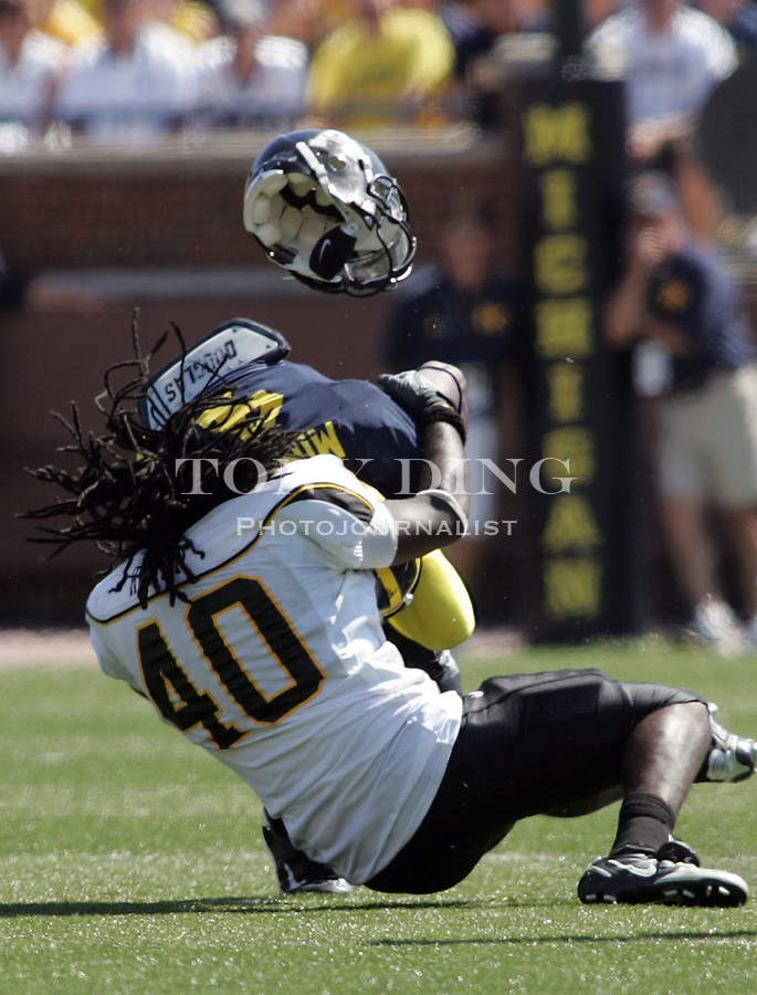 1 September 2007: Appalachian State linebacker Jacque Roman (40) looses his helmet after taking a head-on tackle into the helmet of Michigan ball carrier Brandon Minor, in the 2007 season opener college football game between the Michigan Wolverines and Appalachian State Mountaineers at Michigan Stadium in Ann Arbor, MI. No. 5 ranked Michigan was upset 32-34.
