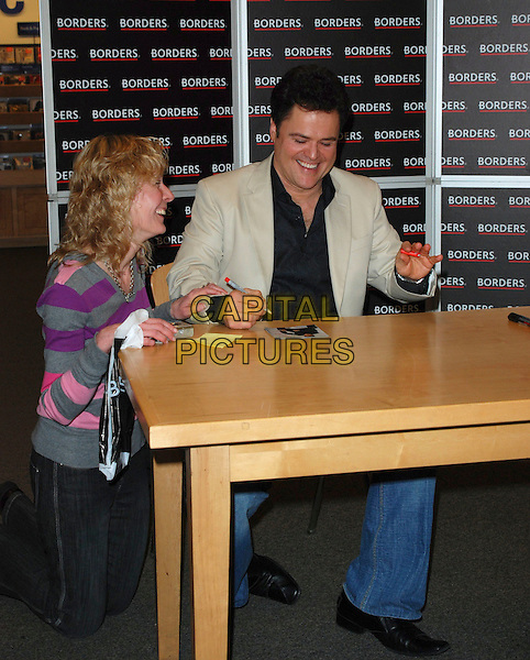 DONNY OSMOND.Signs copies of his new album in Borders Book Shop, Oxford Street, London, England, 9th March 2007..full length black shirt beige jacket sitting table pen autographing signing fan.CAP/CAN.©Can Nguyen/Capital Pictures