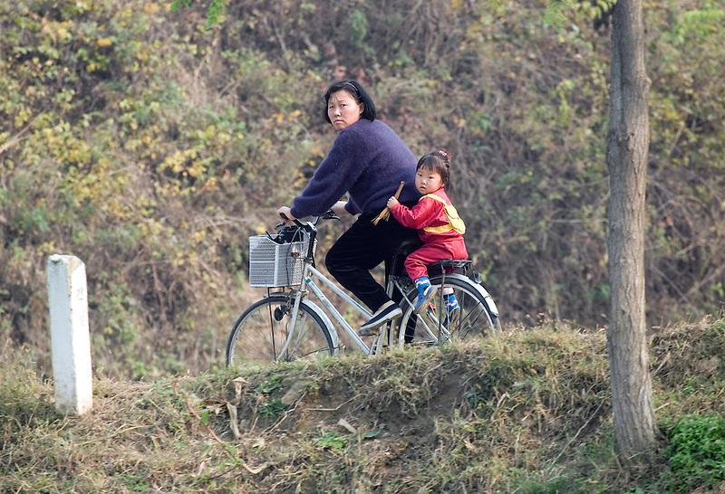 A North Korean woman rides a bike with a small girl near the town of Ch'ongsong Nodongjagu.