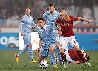 Calcio, Serie A: Roma vs Lazio. Roma, stadio Olimpico, 8 aprile 2013..Lazio midfielder Hernanes, of Brazil, left, is challenged by AS Roma midfielder Michael Bradley, of the United States, as Lazio midfielder Senad Lulic, of Bosnia, center, looks on during the Italian Serie A football match between AS Roma and Lazio at Rome's Olympic stadium, 8 April 2013..UPDATE IMAGES PRESS/Riccardo De Luca