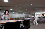 Honda Motor Co.'s humanoid robot ASIMO carries drinks across an office floor during a media demonstration of Honda's new intelligence technologies, which enables the robot to act autonomously and perform uninterrupted services to office guests.