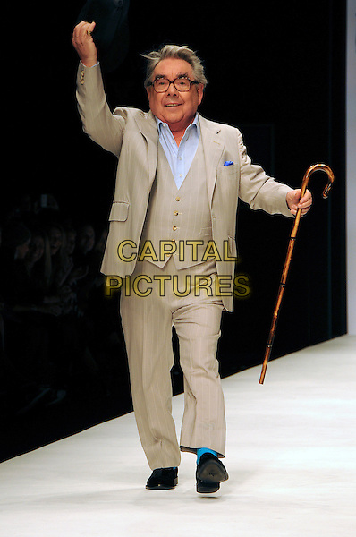 RONNIE CORBETT.The Fashion For Relief Haiti 2010 show for London Fashion Week Autumn/Winter 2010 at Somerset House, London, England..February 18th, 2010.LFW catwalk runway full length black shoes hat beige suit cane glasses arm in air.CAP/CAS.©Bob Cass/Capital Pictures.