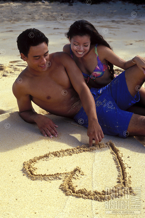 Young couple on the beach at Makena, Maui.  The man show his affection drawing a heart in the sand.
