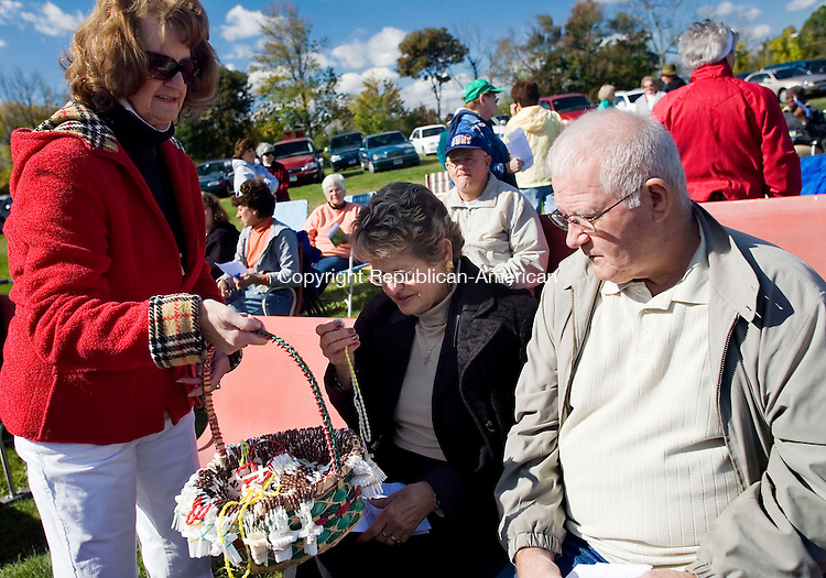 PLYMOUTH, CT-- 13 October 2007--101307TJ06- Barbara Acker, left, from Terryville, offers rosaries to Joyce Rayno, from Southbury, and Bob Barnett, from Bristol as more than 100 people gather at the Terryville Fairgrounds for a public prayer of the rosary, in honor of the 90th anniversary of an apparition of the Virgin Mary at Fatima, Portugal, organized by the Legion of Mary New Britain Curia on Saturday, October 13, 2007. T.J. Kirkpatrick / Republican-American
