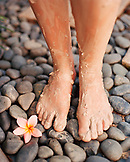 SINGAPORE, Asia, close-up of muddy human legs on spa pebbles with a flower at the Sentosa Resort Spa.