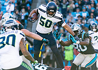 CHARLOTTE, NC - DECEMBER 15: K.J. Wright #50 of the Seattle Seahawks leaps with the ball after an interception during a game between Seattle Seahawks and Carolina Panthers at Bank of America Stadium on December 15, 2019 in Charlotte, North Carolina.