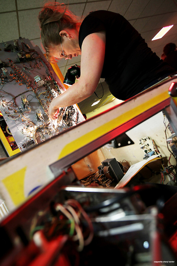 Electrical engineer Sarah St. John, of Pelham, N.H., repairs a pinball game at the 14th Annual International Classic Video Game Tournament in Weirs Beach, N.H., Saturday, June 2, 2012 . (Cheryl Senter for the New York Times)