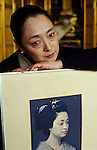 Kyoto, Japan..Mineko Iwasaki, once Kyoto's most famous geisha, at home posing with a photograph of her taken when she was a young geisha...All photographs ©2003 Stuart Isett.All rights reserved.