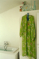 A floaty lime green kimono hangs over the side of a cupboard in the bathroom
