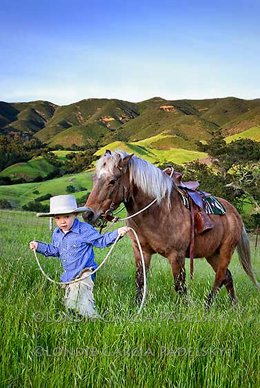 Young cowboy leading his pony in the tall grasses. San Luis Obispo, California