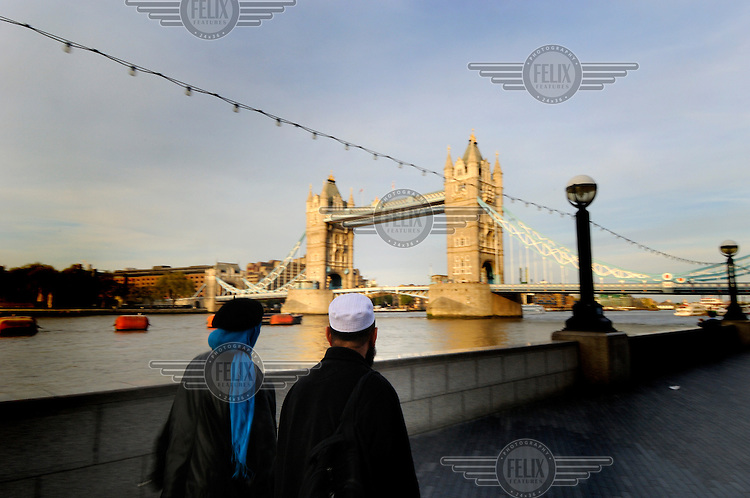 Muslim couple walking along the Southbank of the River Thames in London, with Tower Bridge ahead.